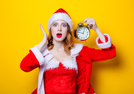 Portrait of Young Santa Clous girl in red clothes with alarm clock on yellow background Stok Fotoğraf - 81491901