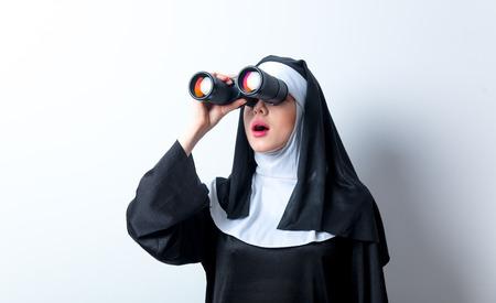 sotana: Joven monja sorprendida con binoculares en busca de algo sobre fondo blanco