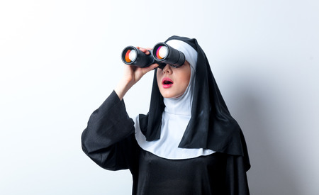 Young surprised nun with binoculars looking for something on white background