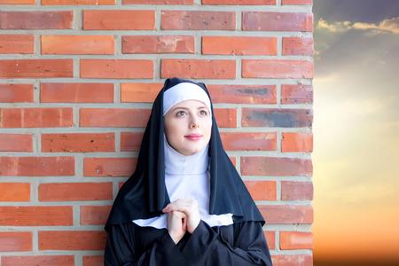 붉은 벽돌 벽 배경에 젊은 웃는 수녀 스톡 콘텐츠