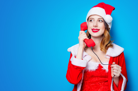 Portrait of Young Santa Clous girl in red clothes with handset on blue background Stok Fotoğraf