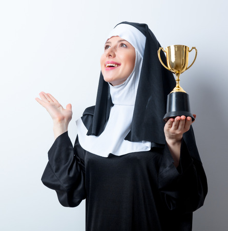 Young smiling nun with golden trophy cup on white background Stock Photo