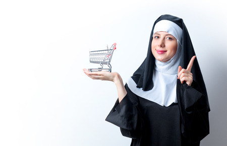 Young smiling nun with shopping cart on white background