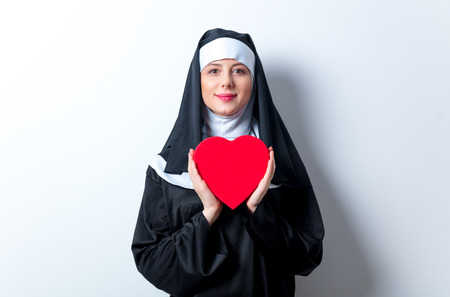 Young smiling nun with heart shape box on white background