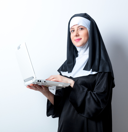 sotana: Young smiling nun with laptop computer on white background