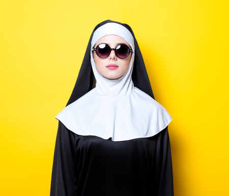 Young nun with sunglasses on yellow background