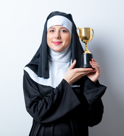 predicador: Young smiling nun with golden trophy cup on white background Foto de archivo