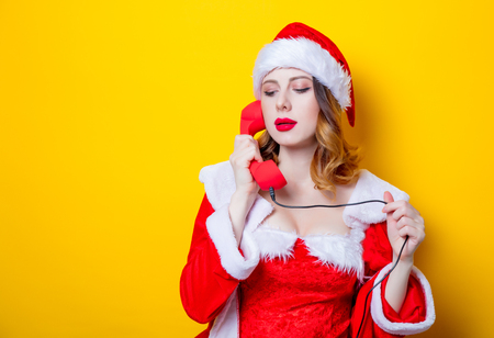 Portrait of Young Santa Clous girl in red clothes with handset on yellow background Stok Fotoğraf