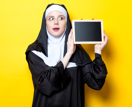 Young surprised nun with board on yellow background