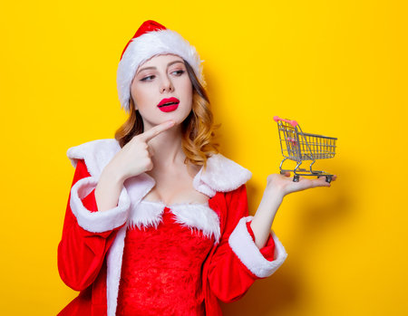Portrait of Young Santa Clous girl in red clothes with shopping cart on yellow background