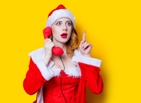 Portrait of Young Santa Clous girl in red clothes with handset on yellow background Stok Fotoğraf - 81491987