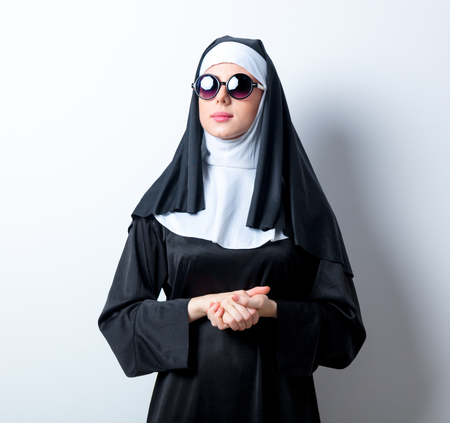 Young serious nun with sunglasses on white background
