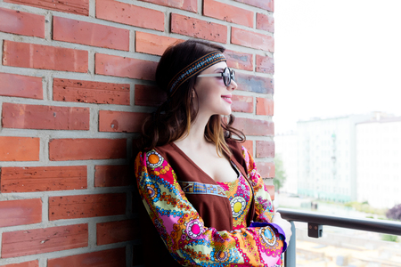 Portrait of Young hippie girl on brick wall background Stock Photo