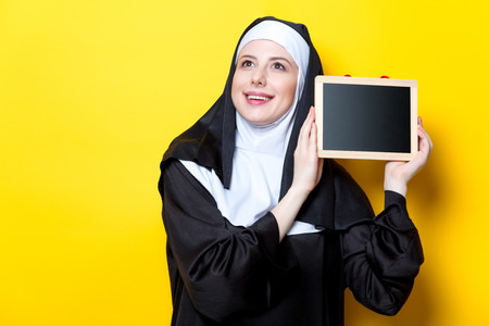 Young smiling nun with board on yellow background