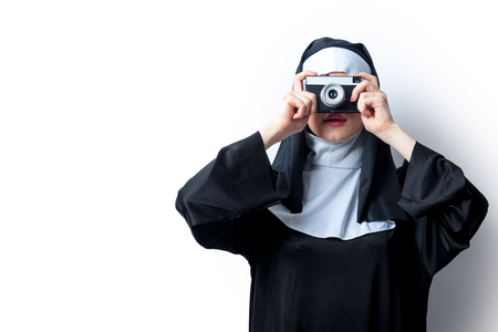 Young smiling nun with photo camera on white background Stock Photo