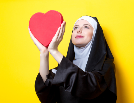 Young happy nun with heart shape box on yellow background Stock Photo