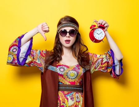 Young hippie girl with sunglasses and alarm clock on yellow background
