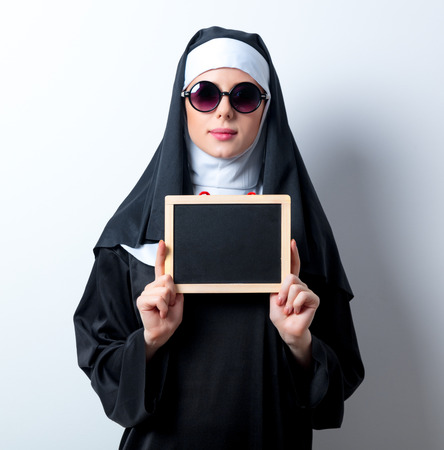 Young serious nun with board on white background Stock Photo