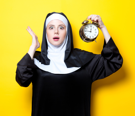 Young surprised nun with alarm clock on white background