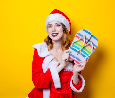 Portrait of Young Santa Clous girl in red clothes with  flip flops on yellow background Stock Photo