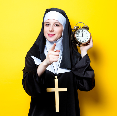 Young happy nun with alarm clock on white background