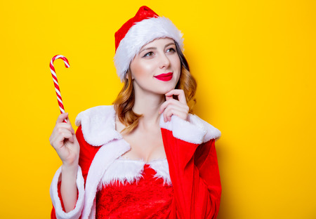 Portrait of Young Santa Clous girl in red clothes with candy on yellow background Stock Photo