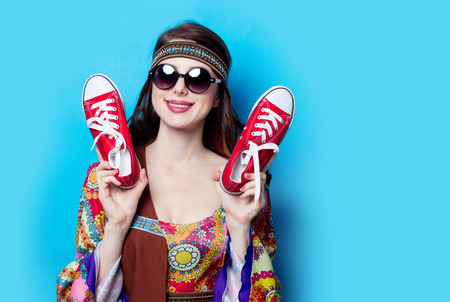 Portrait of Young hippie girl with sunglasses and gumshoes on blue background