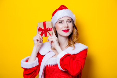 Portrait of Young Santa Clous girl in red clothes with gift box on yellow background