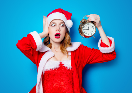 Portrait of Young Santa Clous girl in red clothes with alarm clock on blue background Stok Fotoğraf - 81274104