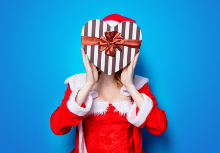 Portrait of Young Santa Clous girl in red clothes with heart shape gift box on blue background Stock Photo