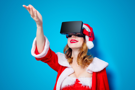 Portrait of Young Santa Clous girl in red clothes with 3D glasses on blue background