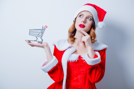 Portrait of Young Santa Clous girl in red clothes with shopping cart on white  background Stock Photo
