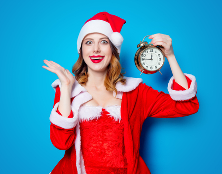 Portrait of Young Santa Clous girl in red clothes with alarm clock on blue background Stok Fotoğraf - 81492088