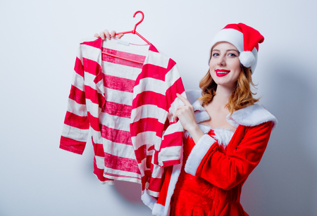 choise: Portrait of Young Santa Clous girl in red clothes with shirt on white background Stock Photo
