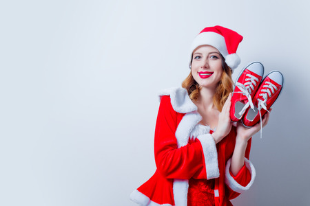 Portrait of Young Santa Clous girl in red clothes with gumshoes on white background Stock Photo