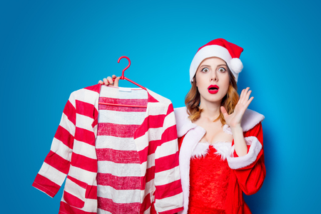 Portrait of Young Santa Clous girl in red clothes with shirt on blue background