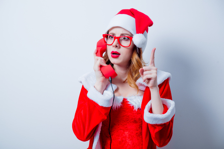 Portrait of Young Santa Clous girl in red clothes with eyeglasses and handset on white background Stok Fotoğraf - 81274204