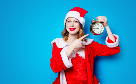 Portrait of Young Santa Clous girl in red clothes with alarm clock on blue background