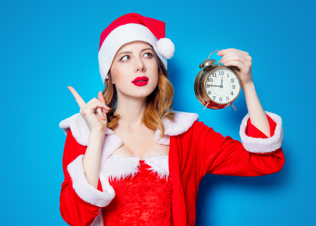 Portrait of Young Santa Clous girl in red clothes with alarm clock on blue background Stok Fotoğraf - 81492097