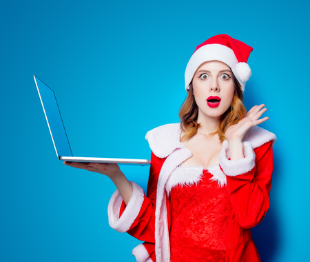 Portrait of Young Santa Clous girl in red clothes with laptop computer on blue background Stock Photo