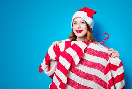choise: Portrait of Young Santa Clous girl in red clothes with shirt on blue background