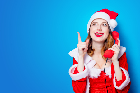 Portrait of Young Santa Clous girl in red clothes with handset on blue background Stok Fotoğraf - 81274279