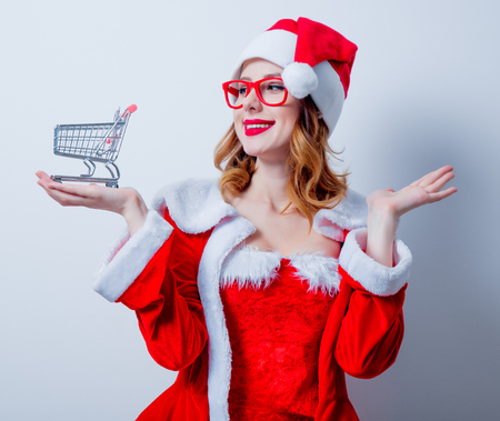 Portrait of Young Santa Clous girl in red eyeglasses with shopping cart on white background Stock Photo