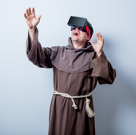 Portrait of Young catholic monk with 3D glasses on white background photo