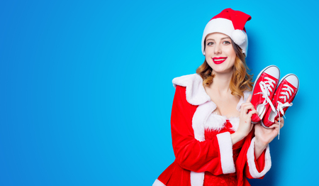 Portrait of Young Santa Clous girl in red clothes with gumshoes on blue background Stok Fotoğraf - 81274352
