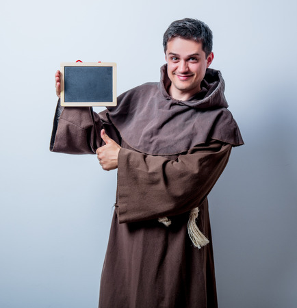 Portrait of Young catholic monk with board on white background photo