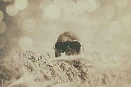 girl with binocular at wheat field. Photo in sepia color image style Stock Photo