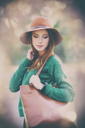 photo of beautiful young woman standing on the wonderful autumn park with bokeh on background