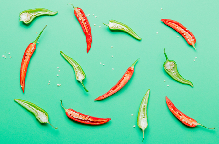 Above view at cutted Chili pepper on green background Stock Photo