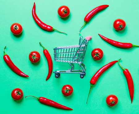 Above view at Chili pepper and shopping cart with tomatoes on yellow background